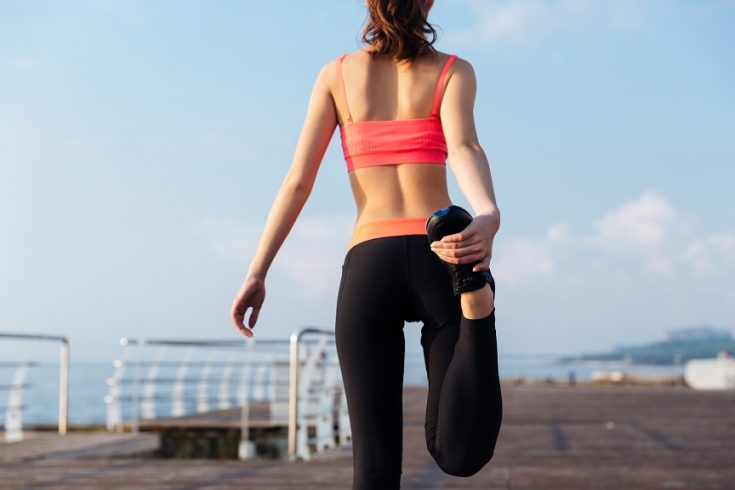 Back view of sportswoman standing and stretching legs on pier