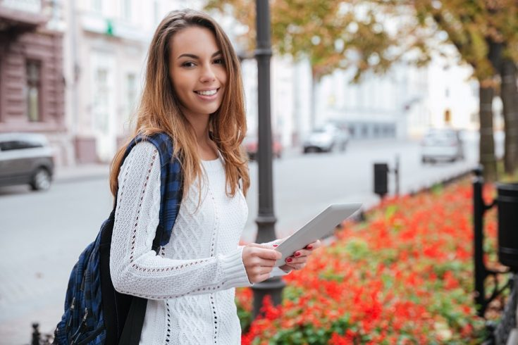 Smiling woman with backpack standing and using tablet in city